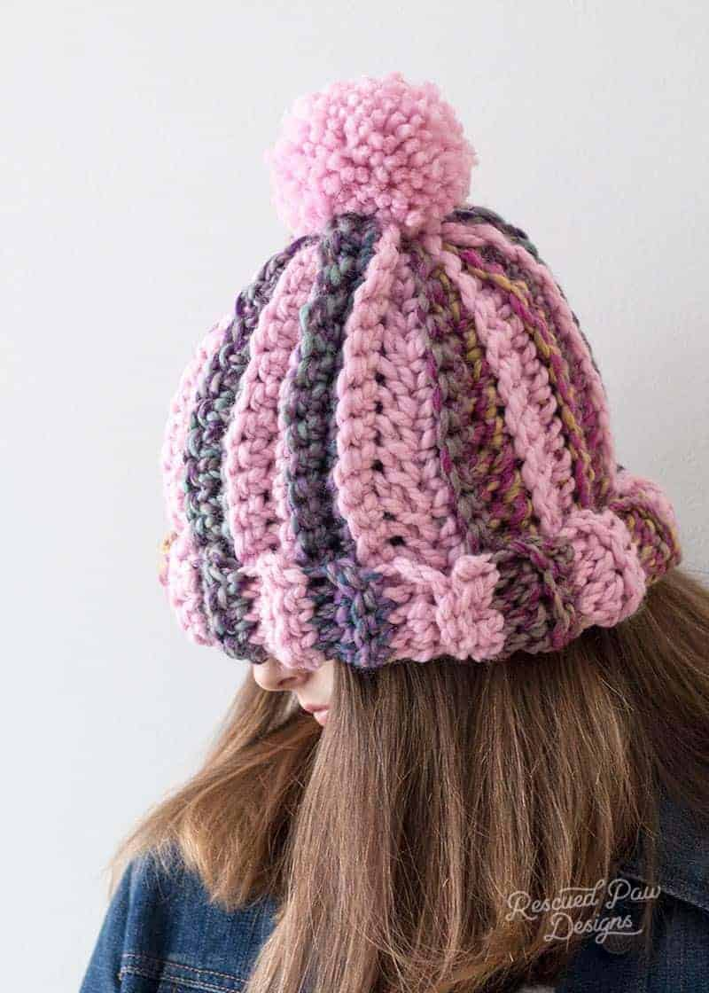 side view of crochet striped pom pom hat